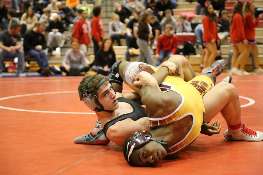 Junior Brett Moon attempts to pin his opponent from Wichita West. Photo by Lyndsey Piska.