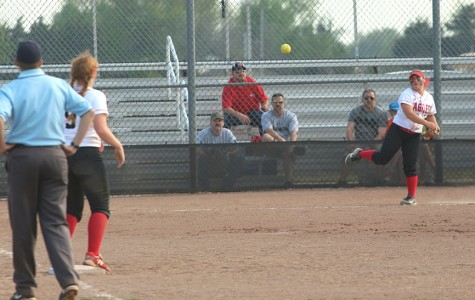 Senior Allie Jergensen throws the ball to sophomore Savannah Hughes between innings.