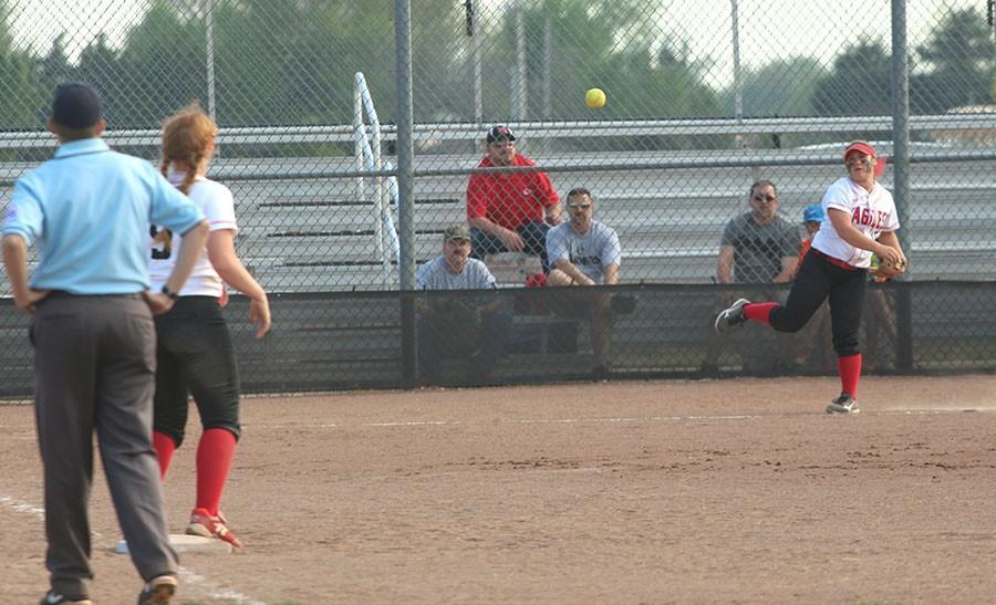 Senior Allie Jergensen throws the ball to sophomore Savannah Hughes between innings.