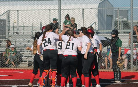 Softball team gathers around junior Savannah Hughes after she hits a home run.
