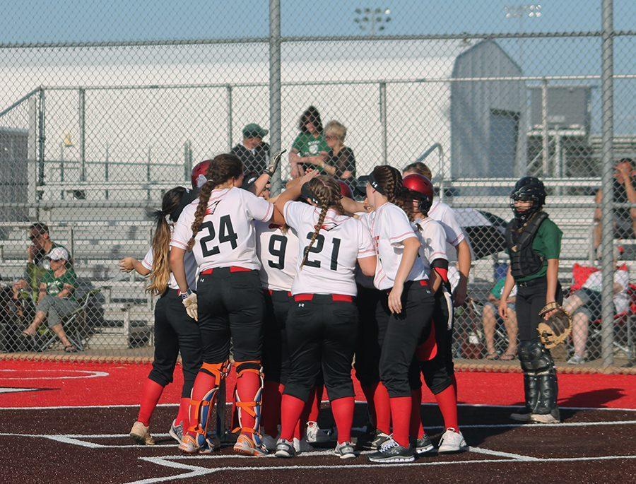 Softball team gathers around junior Savannah Hughes after she hits a home run.