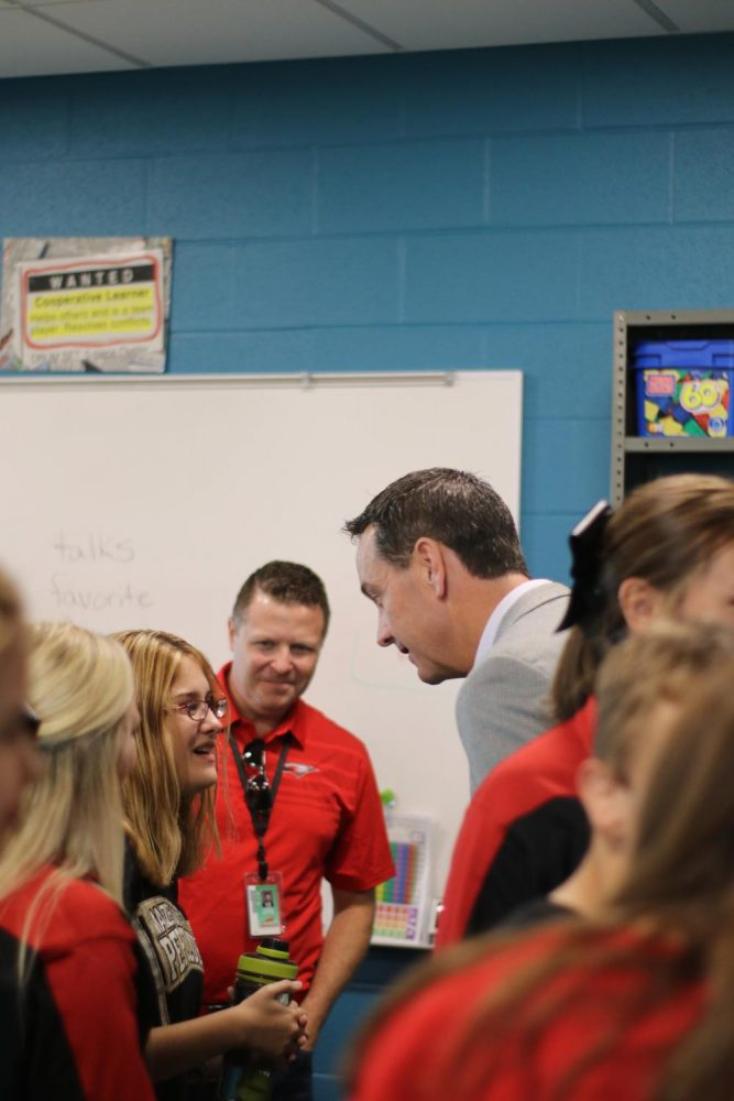 Superintendent Chad Higgins and principal Chris Botts have a conversation with sophmore Alyssa Ramirez. They also attended the friendship club reunion at Maize South.