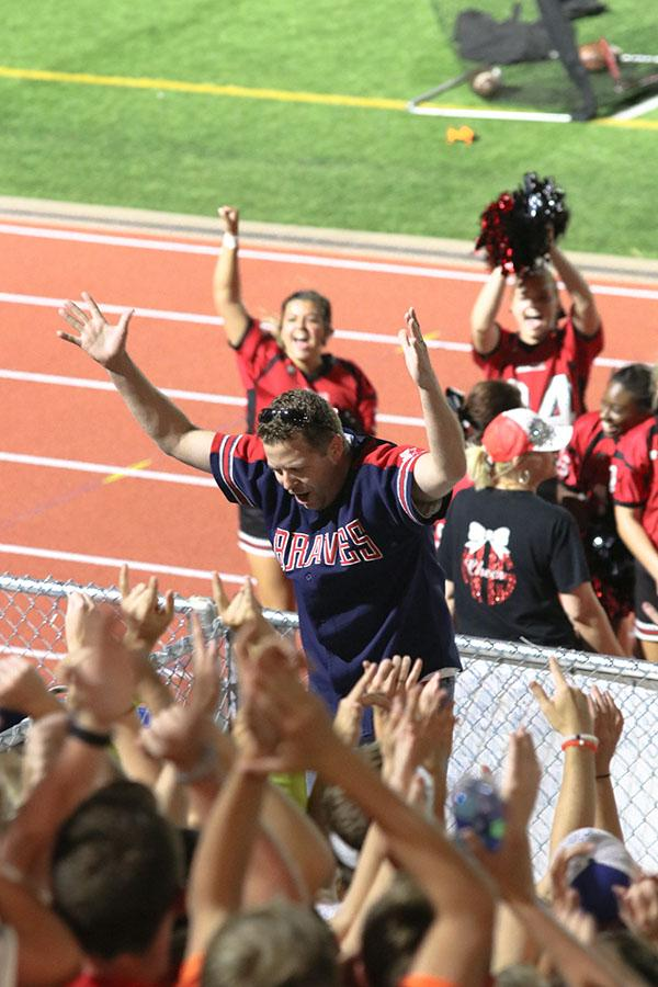 Principal Chris Botts leads the student section in a interactive chant during halftime.