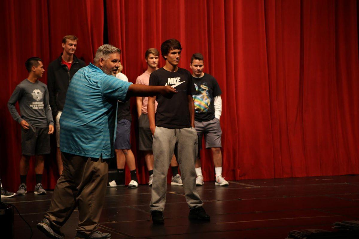 Senior Wyatt Mclaughlin watches as students bid for his soccer jersey.