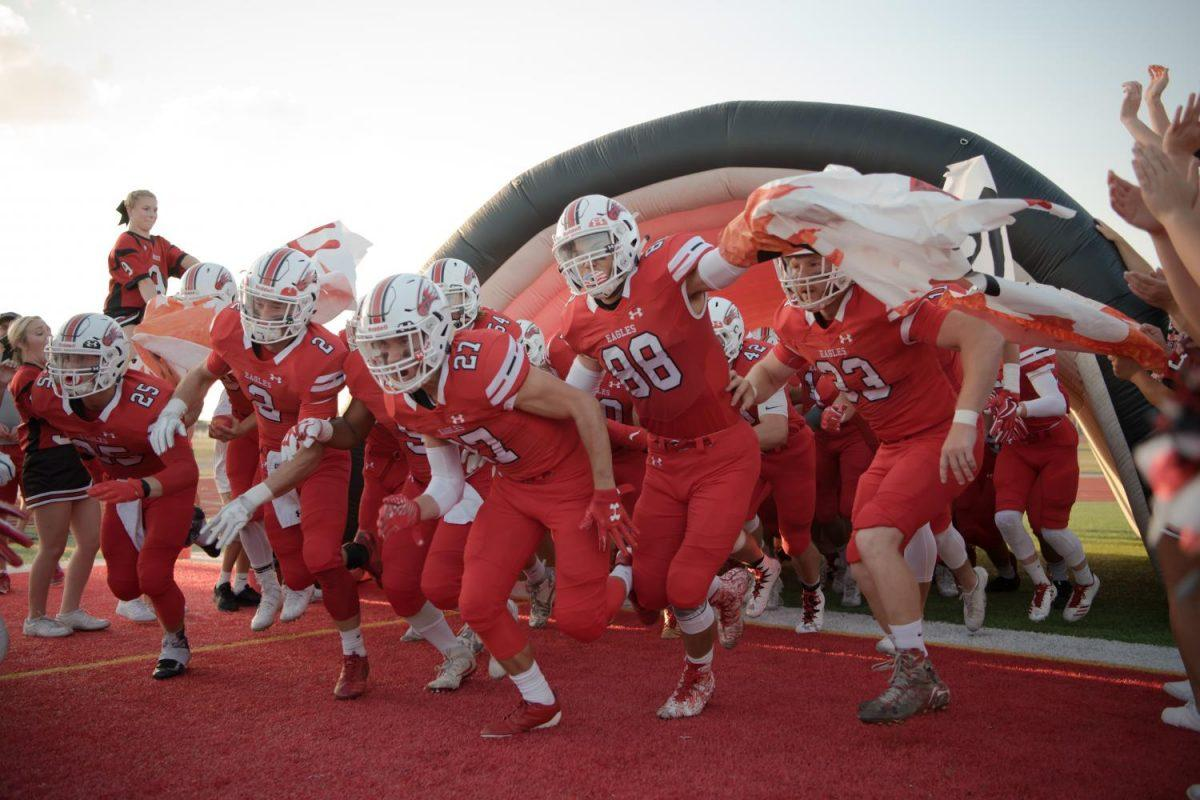 Varsity football players charge the field for the start of the homecoming game.