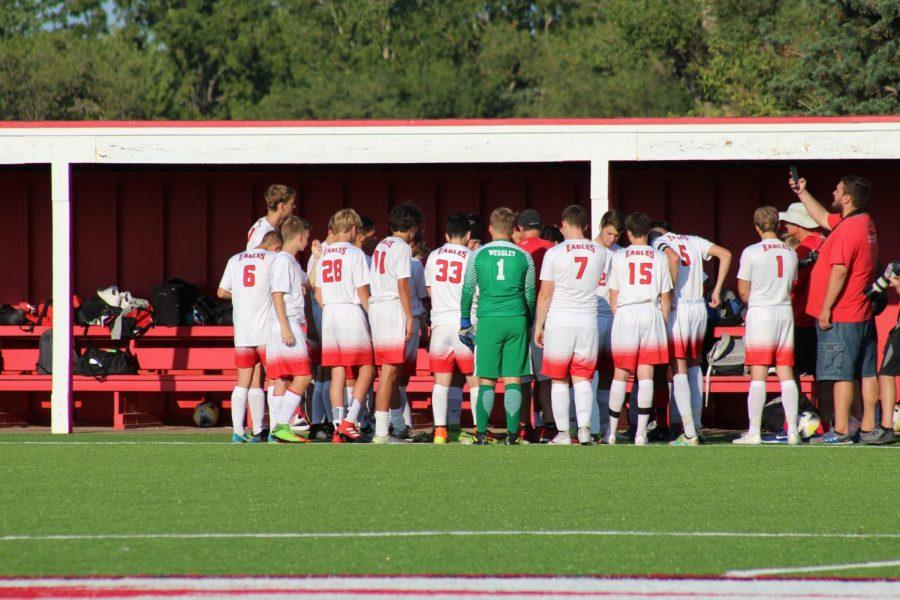 The soccer team huddles up to discuss plays before the game.