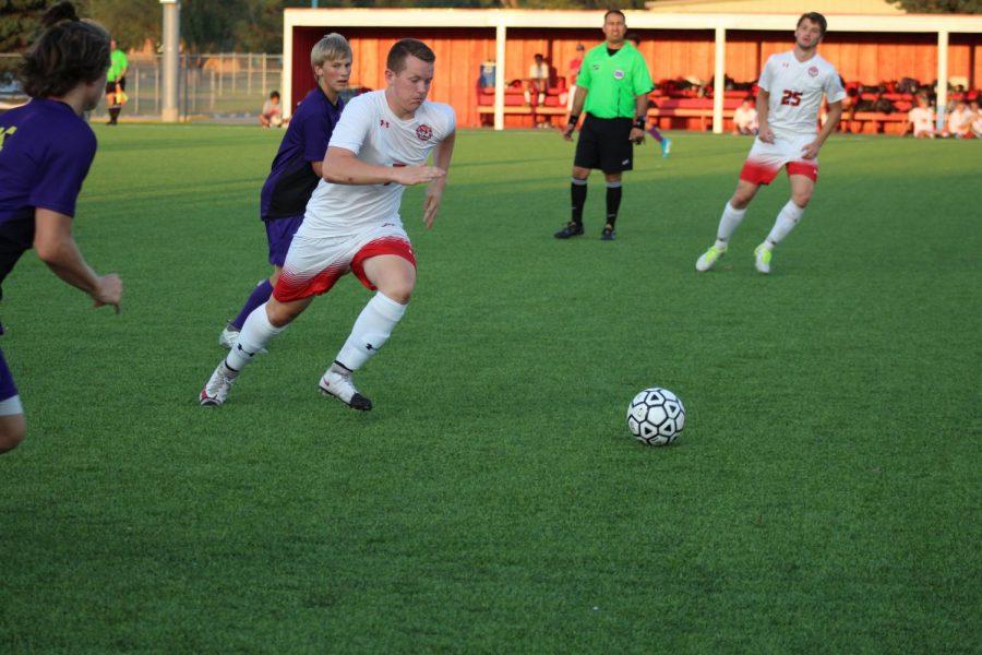 Junior Logan Voran kicks ball toward the goal.
