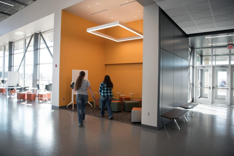 Two students walk to work in the new study nooks. These nooks are outfitted with comfortable chairs, white boards and plenty of working space.