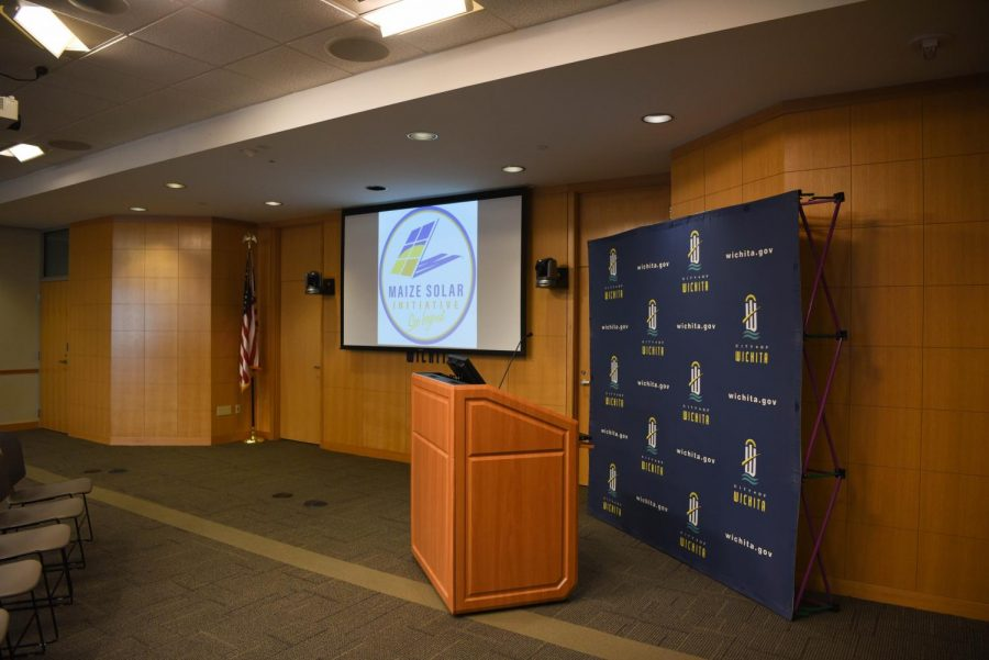 Slide show displays the Solar Initiative logo next to the podium used to speak at the media briefing Thursday morning.
