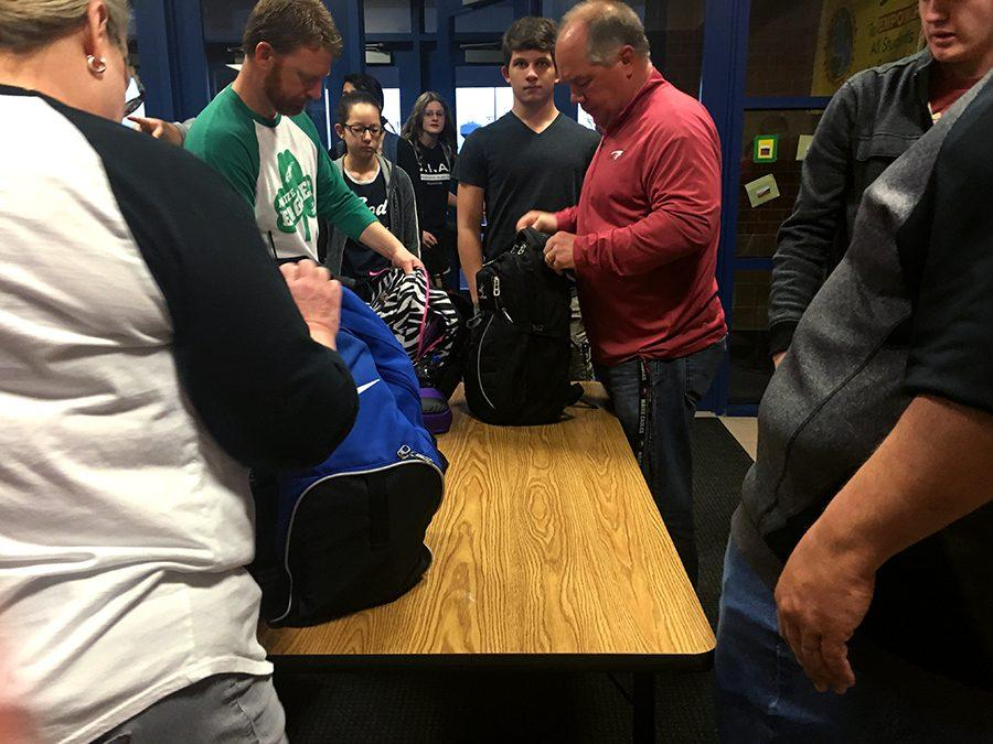 Math teacher Rocky Helm, right, and assistant principal Kevin Frye, left, check students' bags Friday. Security measures were increased after somebody threatened the school.