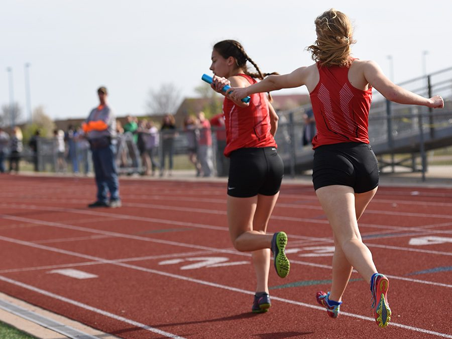 Sophomore Aria Sheldon hands off the baton to senior Tania Allen. The track team competed at the KU Relays on Saturday.