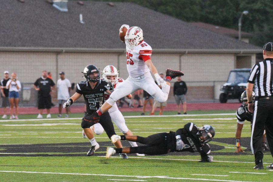 Junior Caden Cox hurdles over Campus defender. The Eagles defeated the Colts 21-0.