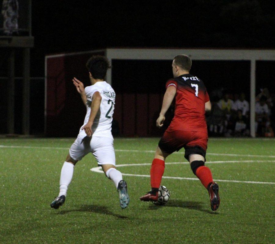 Senior Logan Voran dribbles the ball down the field against opponent.