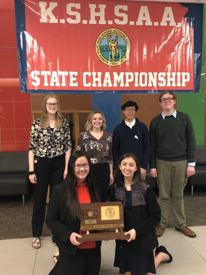 Debate team shows off their trophy after both teams place 3rd at state.