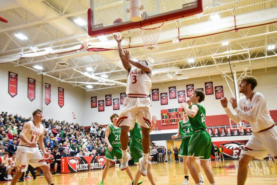Senior Brandle Easter Jr. puts up a lay-up late in the game. The boys and girls teams both won against Bishop Carrol, leaving the boys team still undefeated.