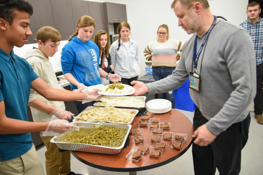 Students serve a meal to an employee. Mashed potatoes, noodles, green beans and frosted brownies were served at lunch.