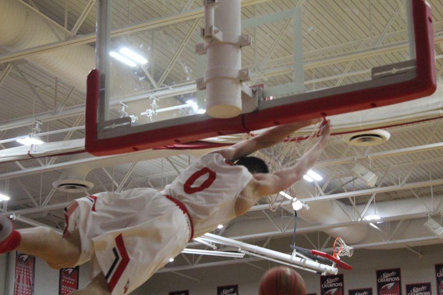 Caleb Grill hangs on the rim after dunking in the second half.