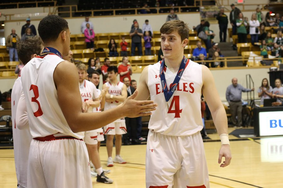 Senior Noah Stanton high-fives Senior Brandle Easter after receiving the third place metal.