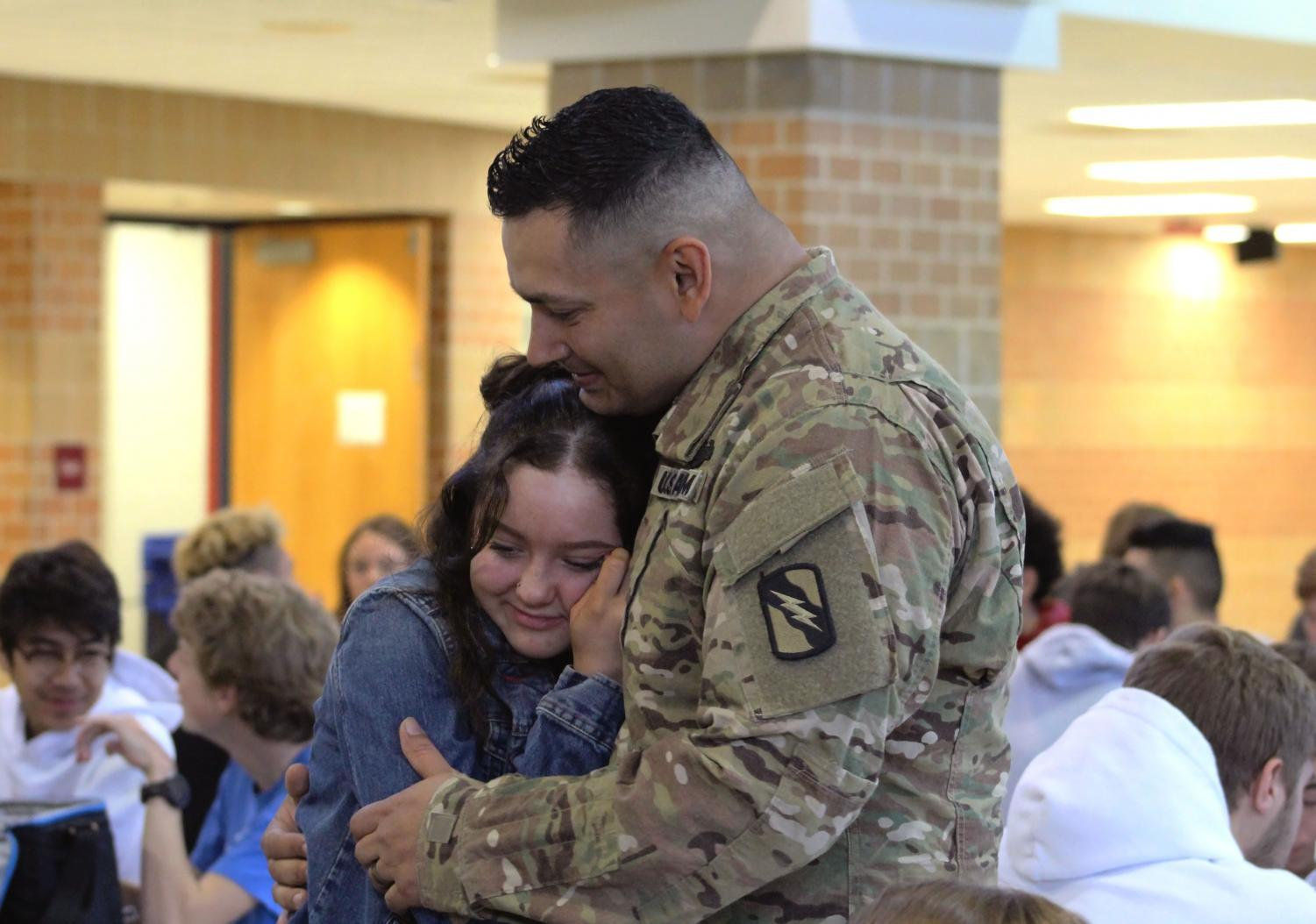 Junior Hannah Martinez smiles in embrace as she reunites with her father. He has been serving for 14 months overseas om the military.