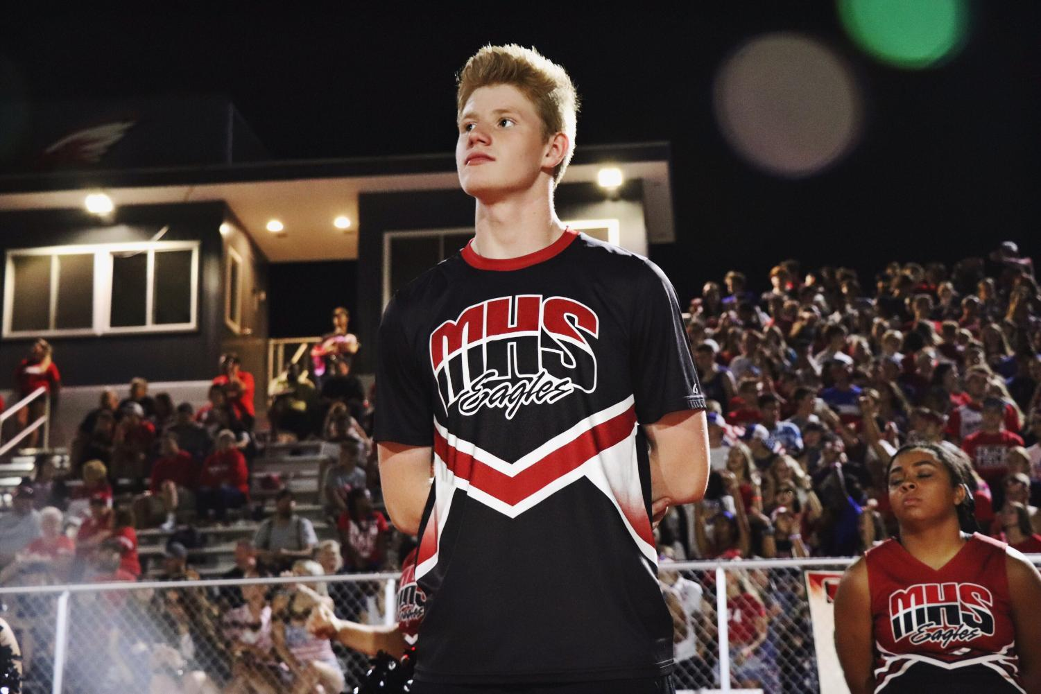 Collin Lee cheers at a football game. Lee has been cheering for eight years.