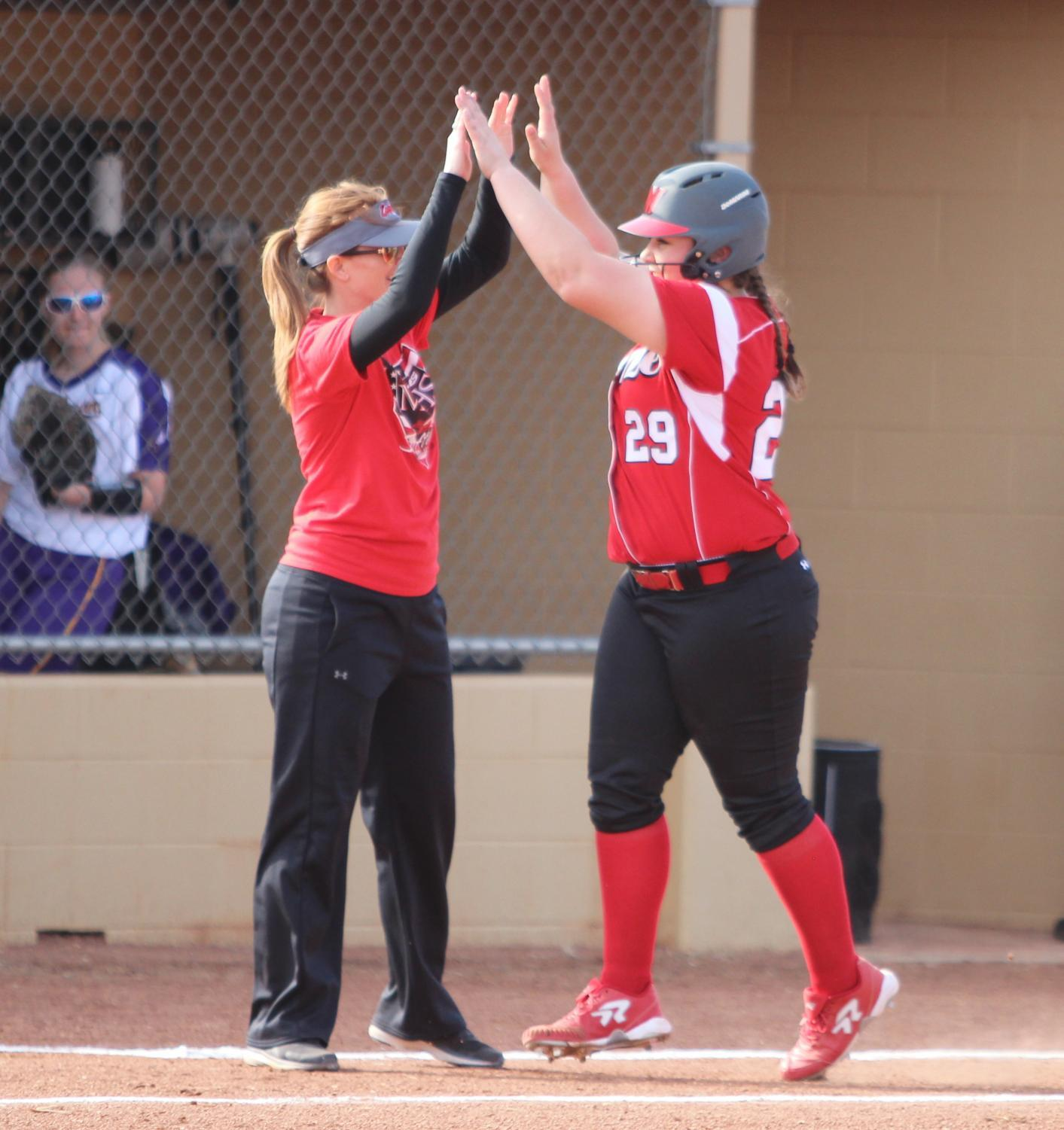 Sophomore Riley Wertz high fives her coach after she scored a home run.