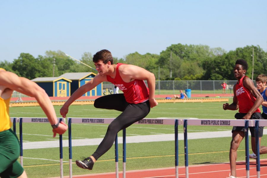 Junior Josh McLaughlin jumps over a hurdle in the 100 meter high hurdles. McLaughlin placed third over all.
