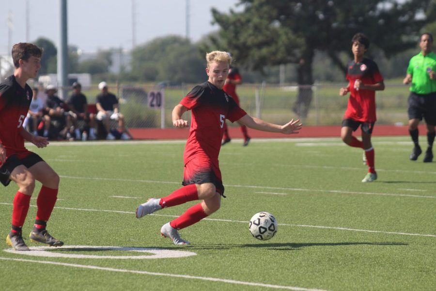 Senior Drew Bott prepares to pass the ball. The soccer team won the first round game of the Titan Classic Tournament with the help of a last-second goal.