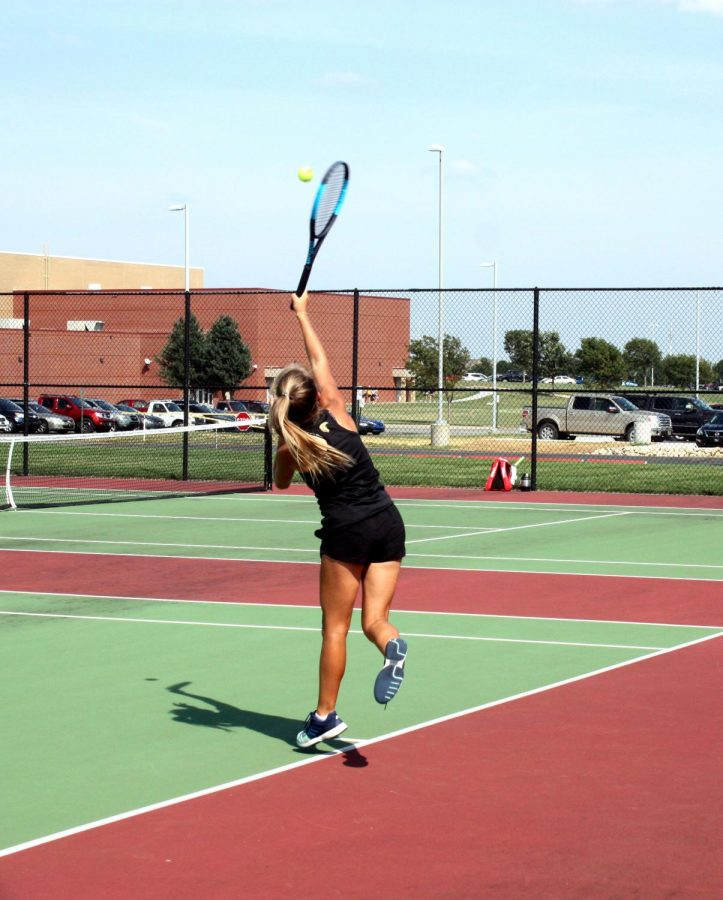 Calissa Brown (12) raises her tennis racket to serve the ball after school on Monday, September 16.