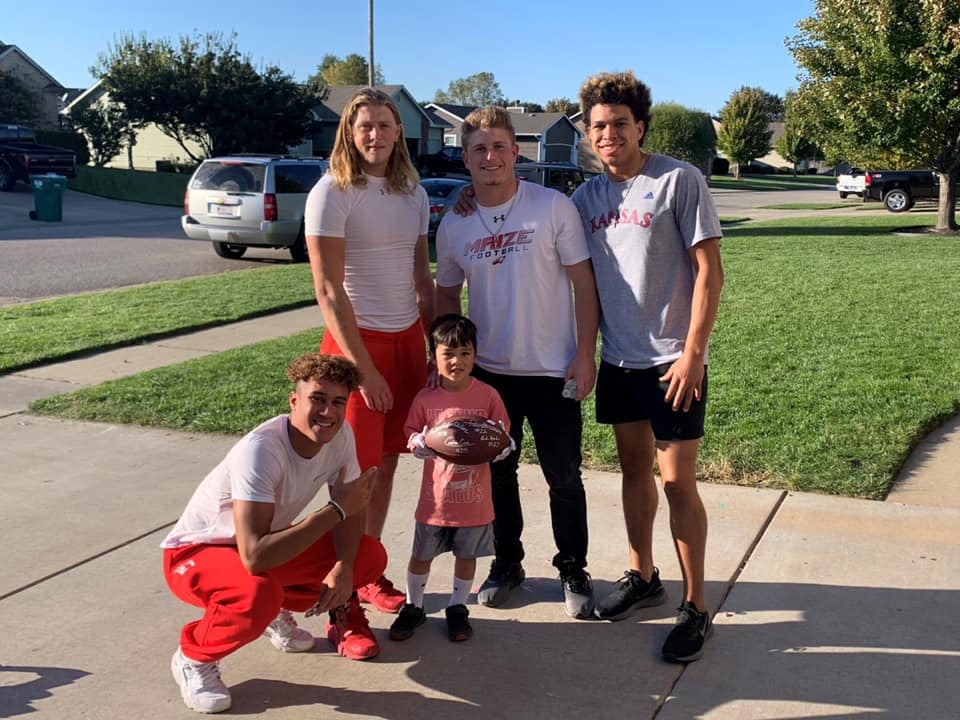 Seniors Caden Cox, Keaton Robertson, Andrew Hanlin and Preven Christon pose with Lucas Vo. The players attended his birthday and gave him a signed football