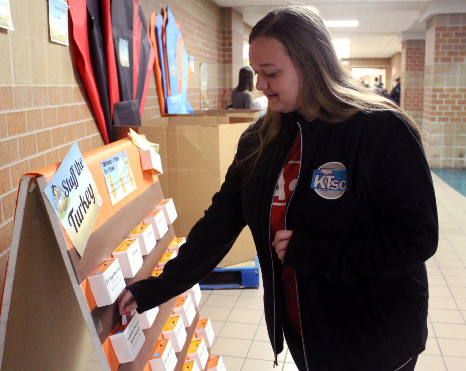Junior Alahni Caldwell places a ticket in one of the teacher's prize boxes. There are a variety of prizes offered, from gift cards to food.