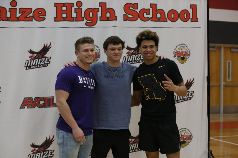 Seniors Caden Cox, Camden Jurgensen, and Preven Christon take a picture after Cox and Christon's signing.