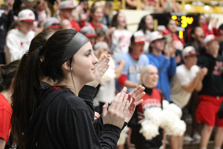 Madi Lambert cheers for her teammates as they close out the first quarter. Lambert came into the game late in the fourth quarter and scored a three-pointer.
