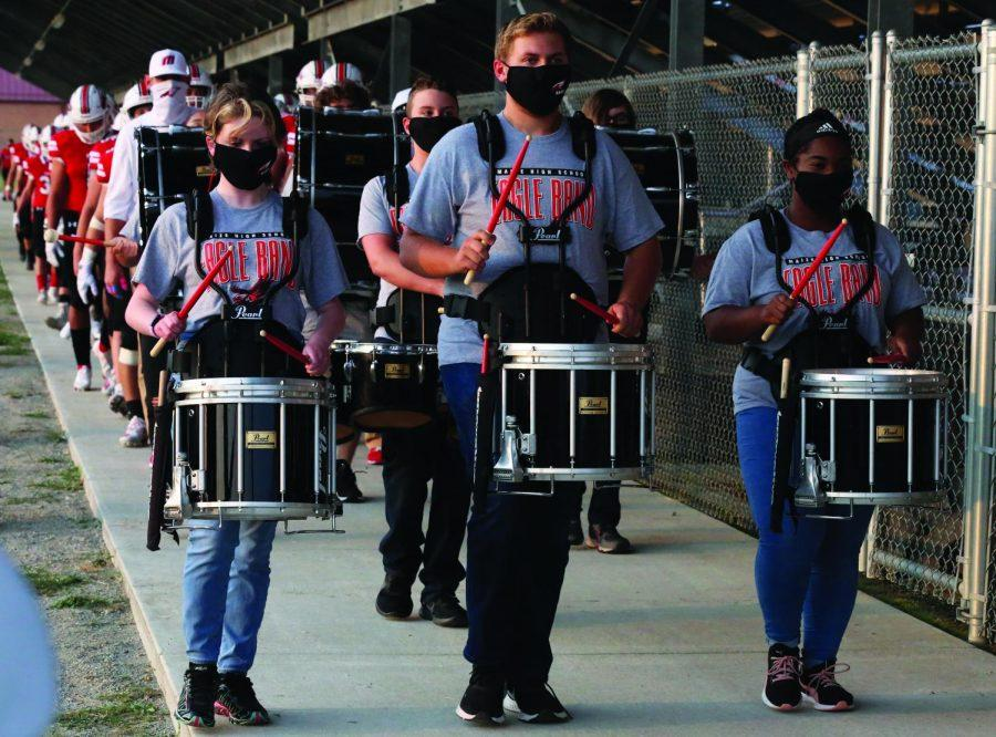 Senior Joshua Avery, junior Kira McGrown and freshman Elsa Dobbs lead the varsity team under the bleachers before the game. Friday was the first time the drumline has played this season.