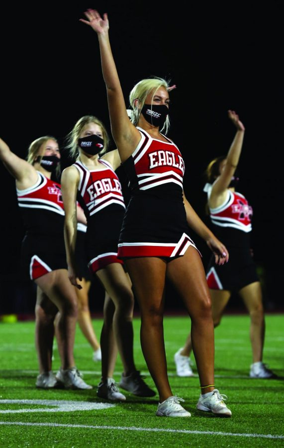 After the cheer performance, senior Kailey Clinton waves to the fans. This is Clinton's fourth year on the team.