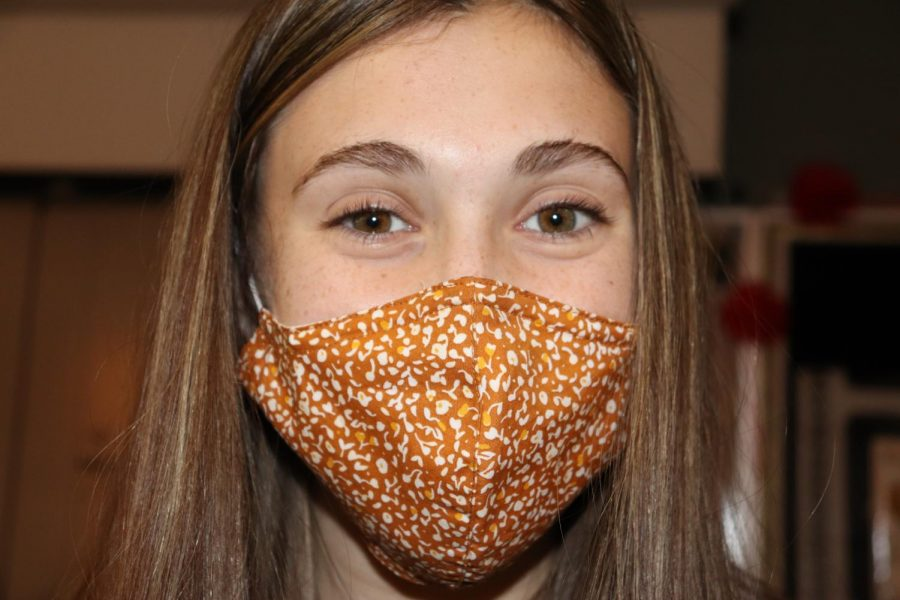 Sporting her favorite gold face mask, freshman Ellyson McAllister shows off her Maverick themed face garment before school to her friend group. McCallister is one of over ten freshmen on this year's Maverick yearbook staff. Photo by Shiah McLain