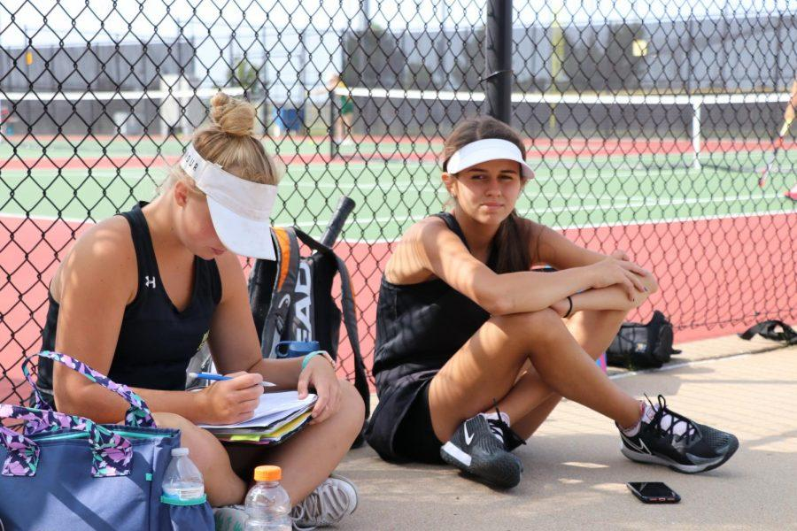 Catching up on some virtual homework before their first matchup, Addison Russell (12) and Madelyn Fellows (09) catch some shade during the 1st round of the Maize South girls home invitational.