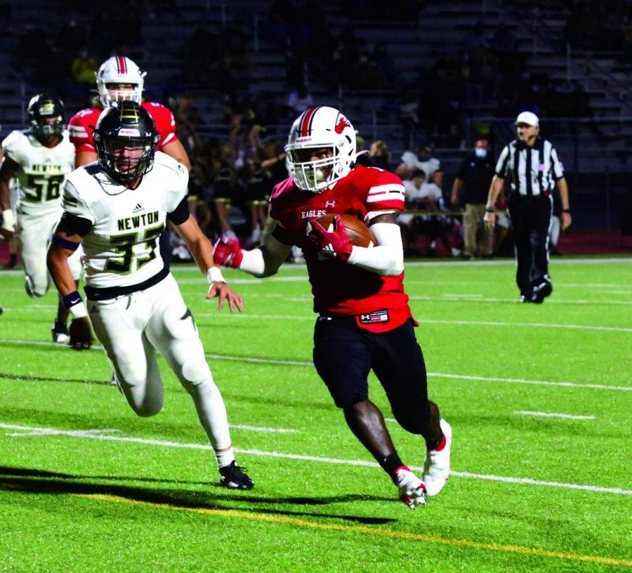 Senior Josh Sanders carries the ball down the field in an attempt to score a touchdown. Sanders scored twice against Newton.