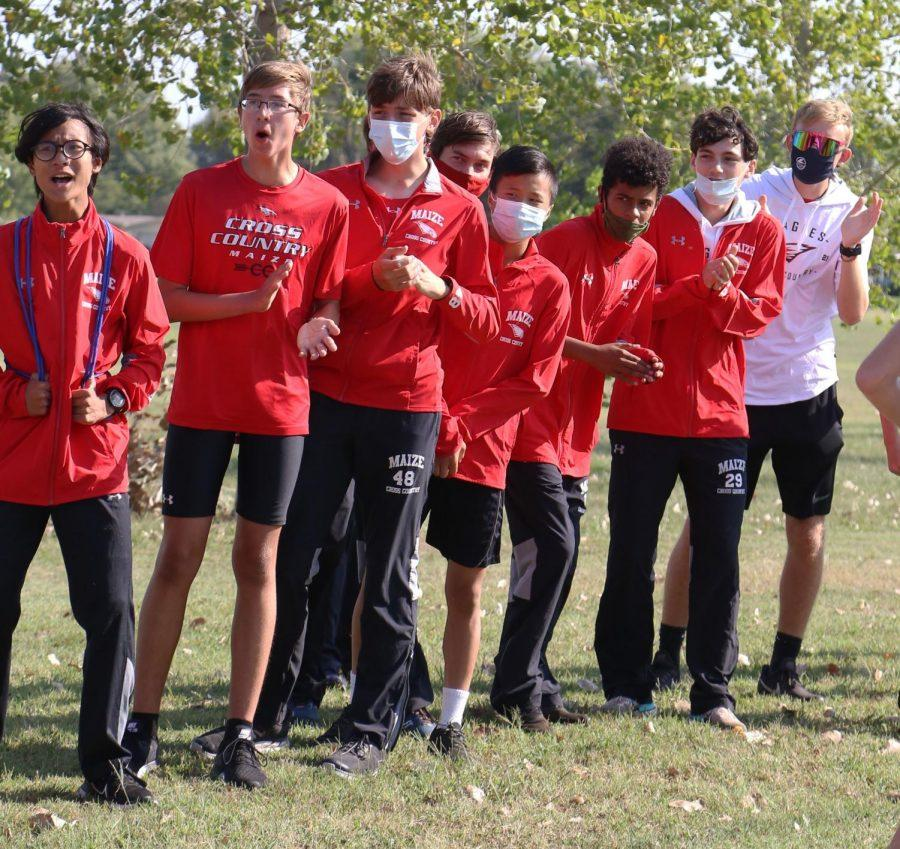 Members of the boys cross country team cheer on their teammates. The meet was held at Brown Thrush Park on Saturday.