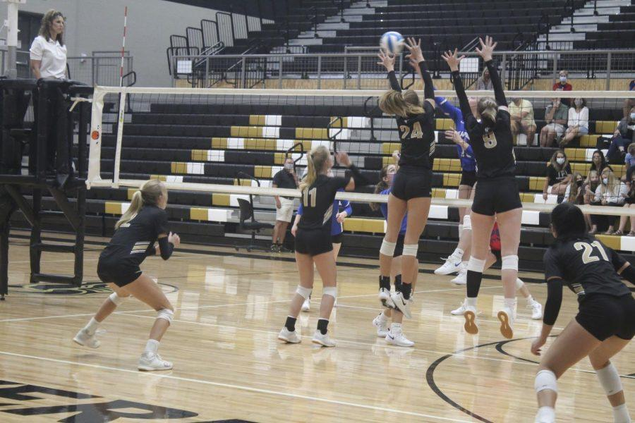 Both jumping into the air at the same time to block the volleyball, Laurel Jones (12), and Avery Lowe (10) attempt to hit the ball back to Kapaun. They missed the shot despite their efforts, but would defeat Kapaun all three matches for the home victory.