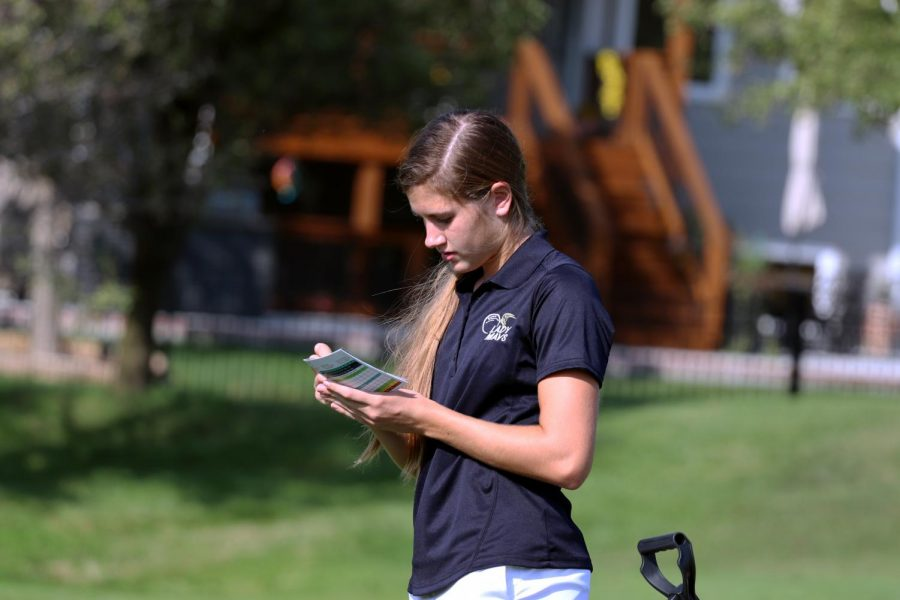 Writing her scores down, Jaden Kordonowy (11) finishes up the last hole in the invitational and  reports her score on a sheet of paper that everyone must have to write their score down after a hole.