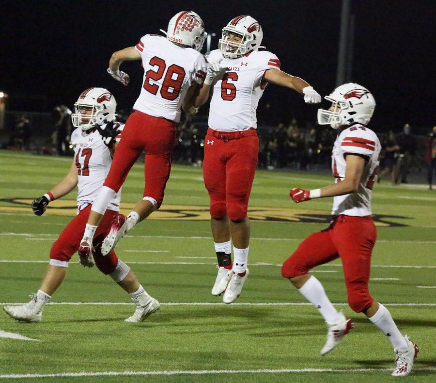 Juniors Cael Moses and Drew Otero celebrate a touchdown during the second half. This two point conversion tied the score.