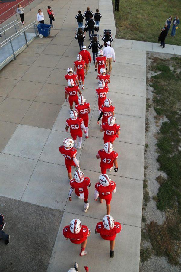 The drumline leadds out the varsity football team before the game. This was the second game the drumline was able to attend following KSHAA rules.