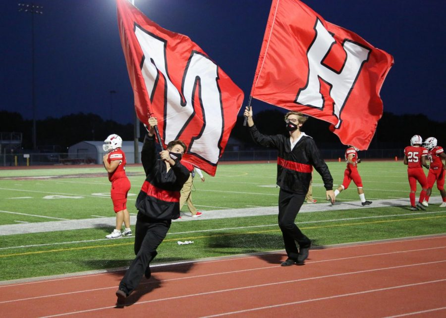 Yell leaders junior Zachary Fullenwider and senior Avery Dover run the flags in celebration of scoring a touchdown.