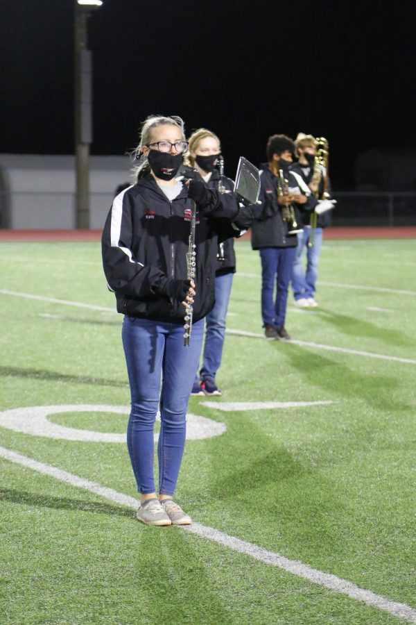 Junior Paige Cannon waits in position for drum major senior Calvin Murrell and band director Shelby Goss.