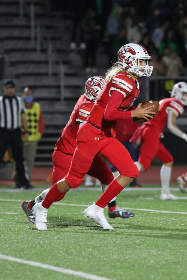 Sophomore quarterback Avery Johnson runs down the field with the ball. This is Johnsons second year playing for Maize.