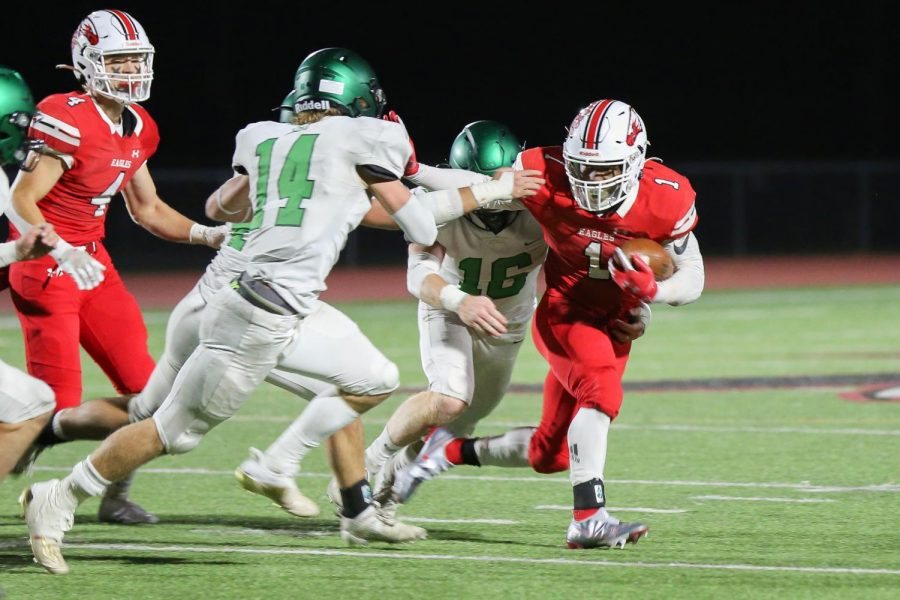 Senior Josh Sanders blocks Derby opponents while driving towards the end zone. Sanders scored three touchdowns in the game.