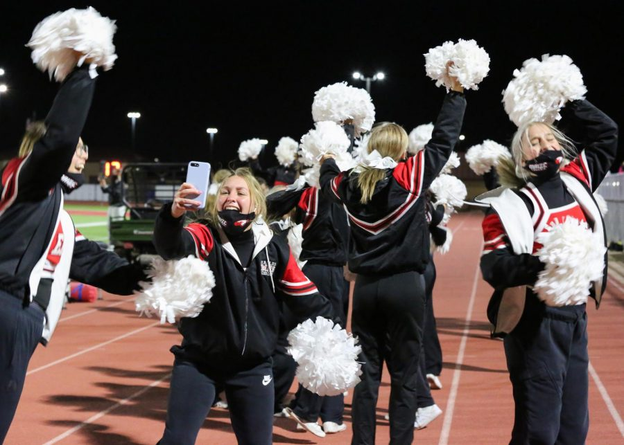 Junior Cora Malone takes a video from the sideline with her fellow cheer teammates in the remaining seconds of the game.