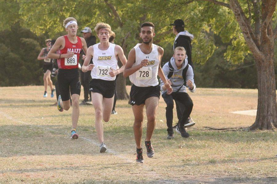 Just passing the halfway point of their 5K, runners Elijah Clark (12) and Austin Schaeffer (11) lead the way for their team.  Schaeffer would take 1st place in the race with a time of 17:05.