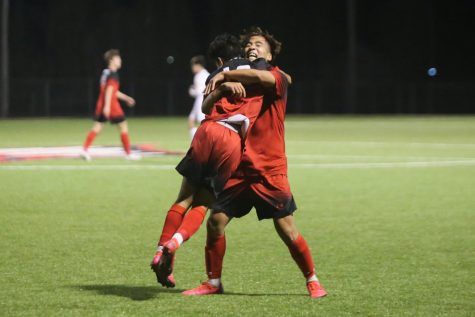 After scoring a goal in the first half, sophomore Angel DeLeon hugs junior Andy Nam. The Eagles beat Great Bend 3-0 and will play Andover Central tomorrow at 4:00 p.m.