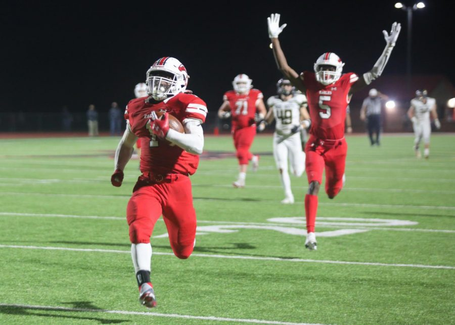 Senior Josh Sanders runs the ball towards the end zone to make the score 59-14. Senior Jacob Hanna celebrates in the background.
